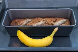 Bananenkuchen gebacken in einer Backform hinter einer reifen Banane platziert