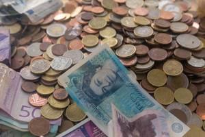 Banknoten und Münzen unterschiedlicher Währungen: Pfund, Euro, Dinar