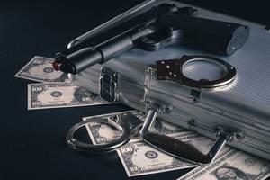 Bankraub-Utensilien mit Pistole, Handschellen und 100 Dollar Scheinen mit einem Geldkoffer