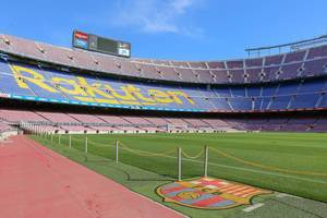 Barrier chain at the soccer field of the Camp Nou stadium and FC Barcelona team logo, with blue-purple tribune in the background, in Spain