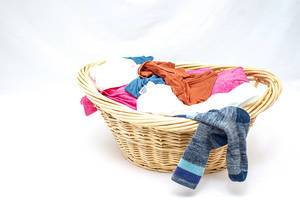 Basket with dirty clothes on a white background