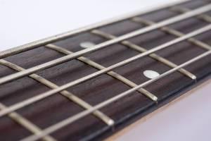 Bass-Gitarrenhals-mit aufgezogenen Saiten vor hellem Hintergrund
