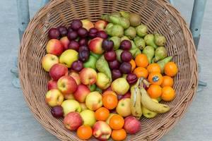 Bastkorb mit verschiedenen ganzen Früchten wie Bananen, Äpfel, Pflaumen, Orangen und Birnen