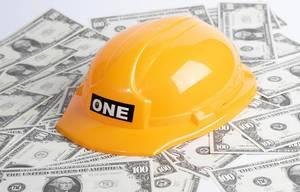 Baugeschäft dargestellt durch gelben Schutzhelm auf verteilten Banknoten