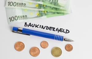 Baukindergeld - Schriftzug mit Kugelschreiber, Geldscheinen und Münzen