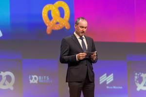 Bayrischer Wirtschaftsminister Hubert Aiwanger hält eine englische Rede vor internationalem Publikum auf der Gründermesse Bits & Pretzels