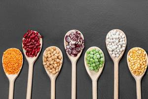 Beans, peas, chickpeas and lentils in wooden spoons on a black background. Top view (Flip 2019)
