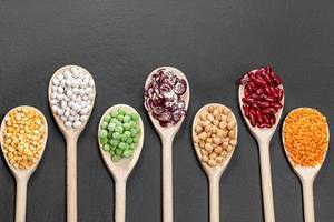 Beans, peas, chickpeas and lentils in wooden spoons on a black background. Top view