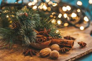 Beautiful Christmas background with spices and blurred glow garland