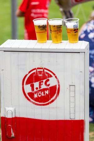 Becher mit Gaffel Kölsch auf einem Schrank mit 1. FC Köln Logo