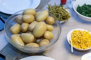 Beilagen zu Raclette wie Pellkartoffeln, Maiskörner, Bohnen und Spinat in verschiedenen  Schüsseln