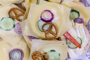Belegte Brötchen mit Käse, Gurke, Bretzel und roter Zwiebel