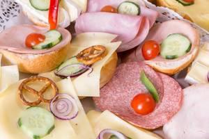 Belegte Brötchen mit Käse, Salami und Schinken mit Gurken und Tomaten