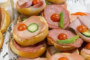 Belegte Brötchen mit Salami und Schinken mit Tomaten und Gurken