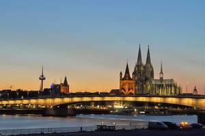 Beleuchtete Brücke und Wahrzeichen einer deutschen Großstadt bei Abenddämmerung