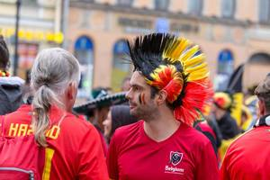 Belgian soccer fan with mohawk haircut dyed in national colors