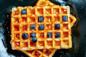 Belgian waffles poured with honey and blueberries. Top view (Flip 2019)