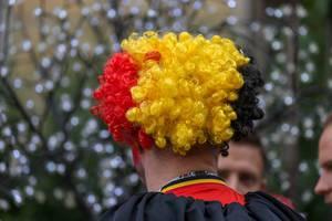 Belgischer Fußballfan mit Perücke in Schwarz, Gelb und Rot