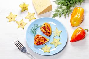 Bell pepper halves baked with tomatoes and cheese on a white wooden background with slices of fresh carambola and dill (Flip 2019)