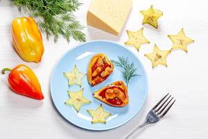 Bell pepper halves baked with tomatoes and cheese on a white wooden background with slices of fresh carambola and dill