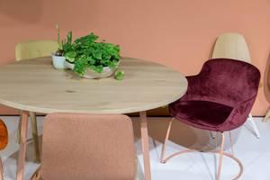 Bequeme, mit weichem Stoff bezogene Stühle stehen um runden Holztisch