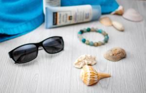 Bereit für den Sommer. Sonnenbrille, Muscheln, Sonnencreme