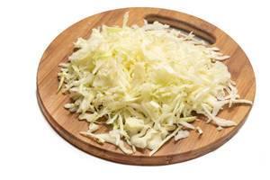 Berg von geraffeltem Weißkohl für Krautsalat auf Küchenbrett aus Holz vor weißem Hintergrund