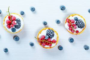 Berry cakes on a white wooden background. Top view