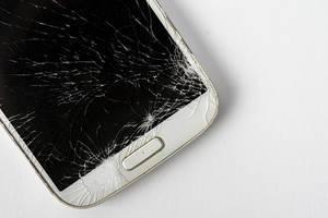 Beschädigtes, zerbrochenes Handy-Display auf einem weißen Tisch, mit Platz für eigenen Text
