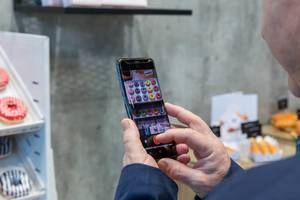 Besucher fotografiert Donuts mit seinem Smartphone bei der Anuga Lebensmittelmesse in Köln
