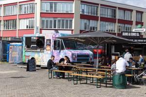 Besucher genießen ihr Essen und Getränke beim Food-Festival