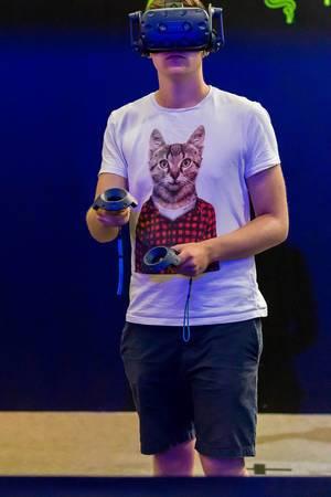 Besucher mit Katzen-Shirt spielt mit VR Headset und Controllern