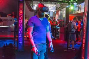 Besucher spielt Hologate mit VR Headset und Controllern von HTC