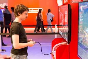 Besucher spielt mit dem Pro Kontroller auf der Nintendo Switch - Gamescom 2017, Köln