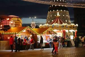 Besucher und beleuchtete Hütten auf dem Weihnachtsmarkt in Bucharest, Rumänien, Nachtsaufnahme