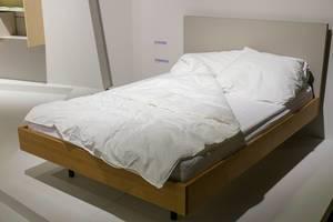 Bett mit Holzrahmen, Kissen und Decke in Ausstellungsraum