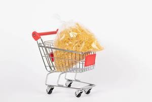 Beutel mit dünner Pasta liegt in Einkaufswagen vor weißem Hintergrund