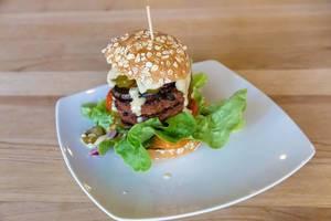 Beyond Meat Burger auf weißem Teller auf einem Holztisch in Bunte Burger Köln