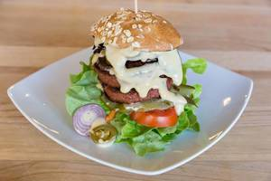 Beyond Meat burger with Portobello mushroom bacon and fresh vegetables on the wooden table of Bunte Burger Cologne