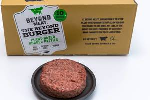 Beyond Meat Patty - a vegan, gluten free alternative of burger meat on black plate with its package in the background