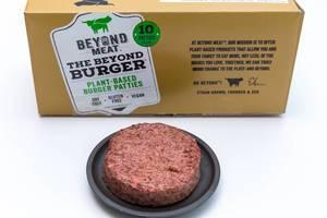 Beyond Meat Patty - eine vegane, glutenfreie Alternative zum Burger-Fleisch - auf schwarzem Teller mit der Packung im Hintergrund