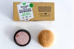Beyond Meat veganisches glutenfreies Burger-Pastetchen auf schwarzem Teller mit Burger-Brötchen nebenan