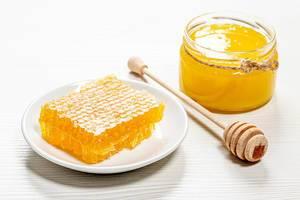 Bienenprodukte mit Honig und Honig-Wabe auf weißem Hintergrund - Gesundheitsprodukte mit organischen, natürlichen Inhaltsstoffen