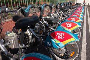 Bike sharing: rental bikes in a row at a station with just eat advertising cover