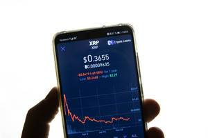 Bildschirm eines Mobiltelefons zeigt Ripple (XRP) Marktwert vor weißem Hintergrund