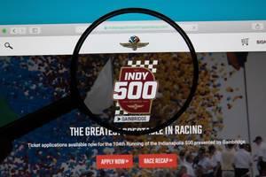 Bildschirm zeigt Internetseite des Motorsport-Events in Indianapolis mit Lupe über Logo des Indy 500