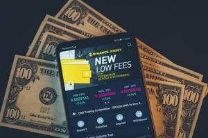 Binance Kryptopwährungs-Wechsel App auf einem Handydisplay mit einhundert Dollarnoten