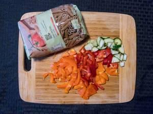 Bio Penne und geschnittene orangefarbene und rote Paprika und Gurke