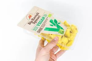 Bio, vegan und laktosefrei: Hand hält Ravioli mit Spinat von Mosna in transparenter Verpackung vor weißem Hintergrund