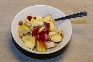 Biologisches Vanille-Chia Porridge mit Äpfeln, Bananen und verschiedenen Nüssen in weißer Schale